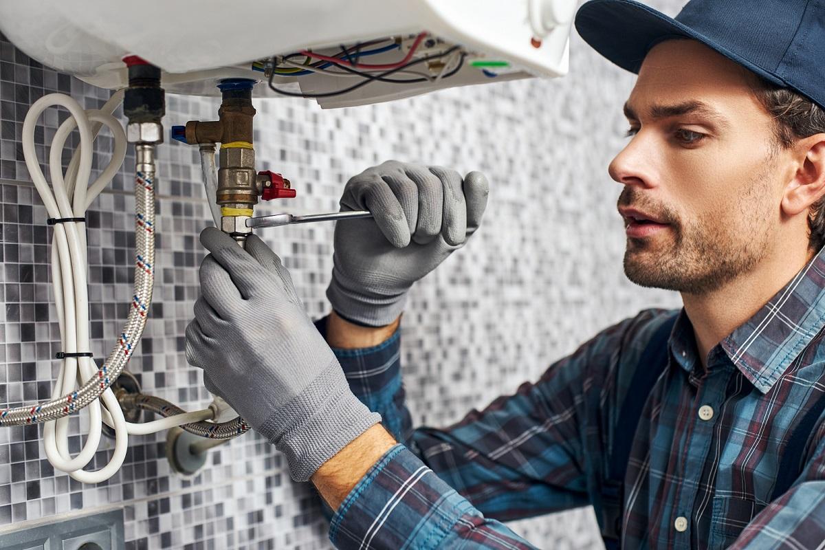 Worker set up electric heating boiler at home bathroom